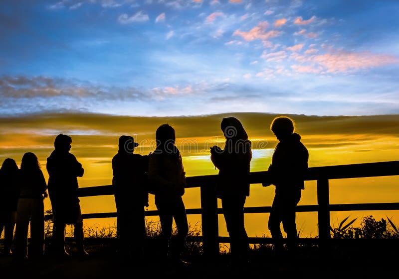 I turisti delle siluette stanno osservando l'alba il punto di vista fotografia stock