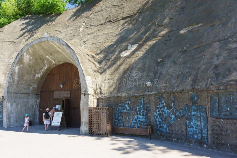 I turisti entrano nella grotta del negozio aziendale, le pareti di cui sono decorate con i graffiti che descrivono la storia del  immagine stock