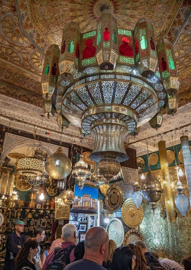 I turisti esplorano gli oggetti dell'abbagliamento in Fes Souk fotografia stock libera da diritti