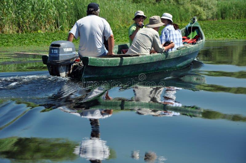 I turisti fanno il viaggio della barca nella riserva di biosfera di delta del Danubio immagini stock libere da diritti