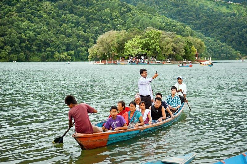 I turisti godono del giro nel vasto lago Phewa, colori naturali della barca immagini stock