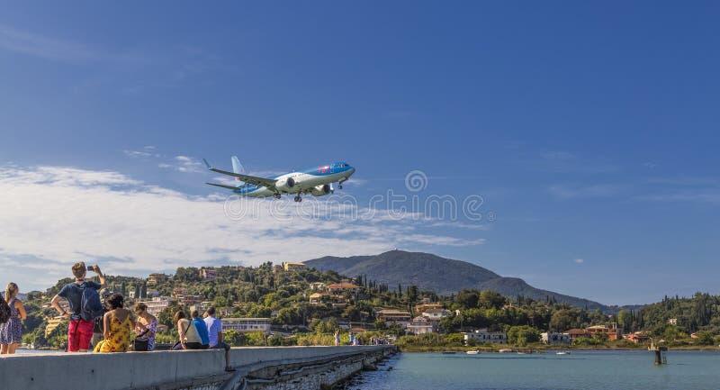 I turisti guardano l'aereo Boeing 737 MAX 8 della Tuifly Belgium atterrato sulla pista dell'aeroporto Kerkira Ioannis Kapodistria immagini stock libere da diritti