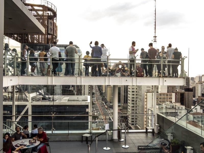 I turisti osservano la vista della regione di viale di Paulista dal terrazzo di Sesc Avenida Paulista immagini stock libere da diritti