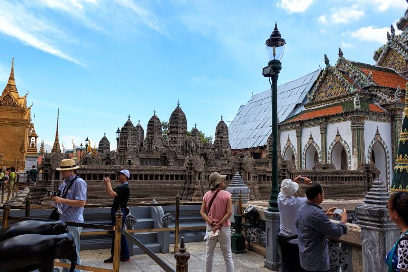 I turisti osservano una replica del Angkor Wat Palace in Royal Palace di Bangkok immagini stock