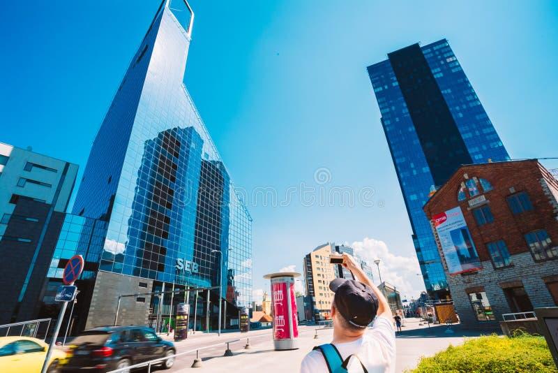 I turisti prendono le foto dei grattacieli blu di vetro e di calcestruzzo I immagini stock libere da diritti