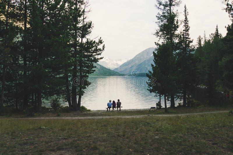 I turisti si siedono su un banco sulla riva del lago alpino fotografie stock