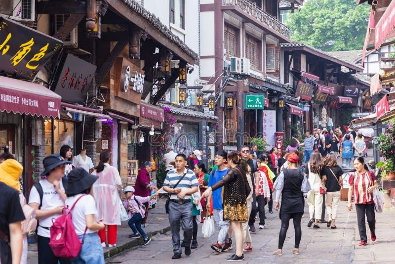 I turisti sono passeggiata per la compera nella città antica di Ciqikou, una destinazione popolare di viaggio fotografie stock libere da diritti