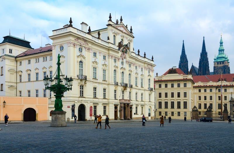 I turisti sono sul quadrato di Hradchanskaya a Praga, repubblica Ceca Vista del palazzo dell'arcivescovo, castello di Praga immagine stock libera da diritti