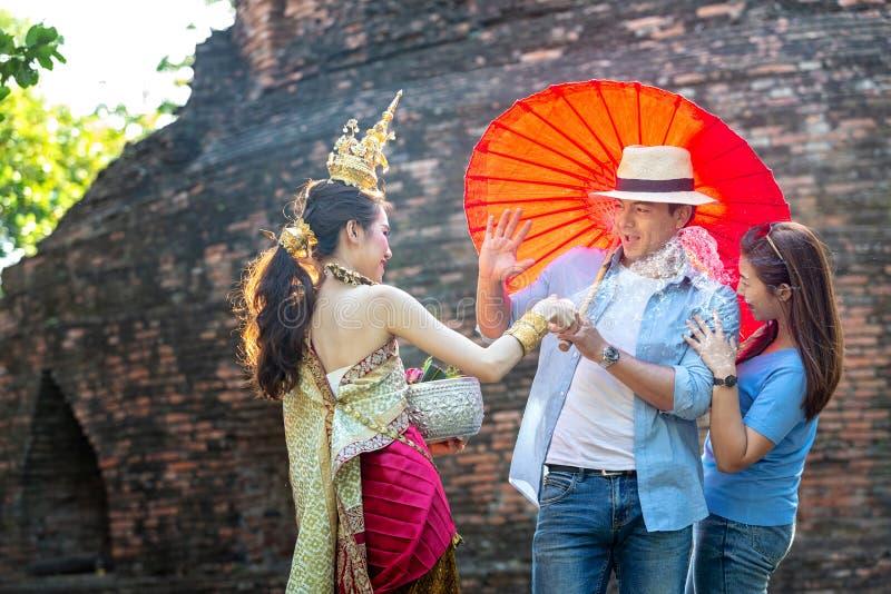 I turisti stanno godendo del festival di Songkran Ragazze tailandesi e giovane uomo caucasico che spruzzano acqua durante il fest fotografie stock