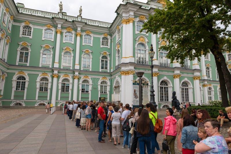 I turisti stanno nella linea davanti all'entrata per visitare le mostre del Museo dell'Ermitage dello stato immagini stock libere da diritti