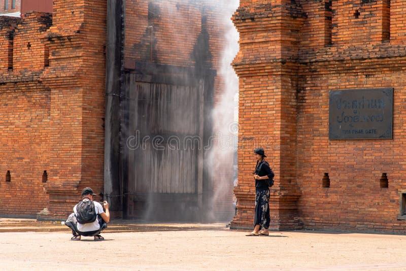 I turisti stanno prendendo le foto al portone di Thapae con lo spruzzo d'acqua fotografie stock libere da diritti