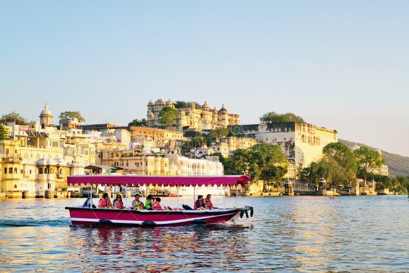 I turisti sulla barca che prende la barca del tramonto di Pichola del lago Udaipur guidano con il palazzo della città su fondo fotografia stock
