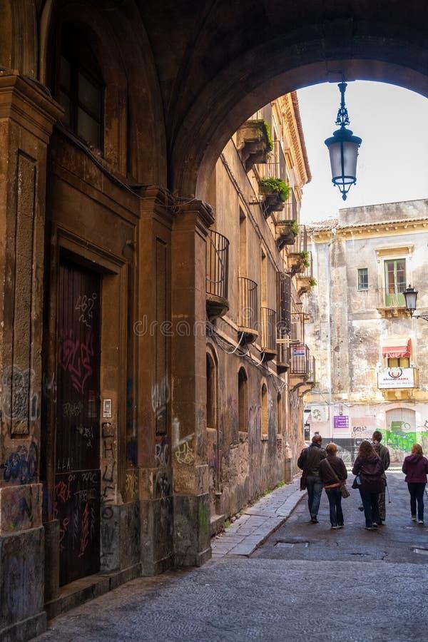 I turisti vagano tramite i vicoli antichi di Catania in Sicilia fotografia stock libera da diritti