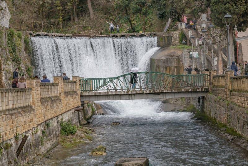 I turisti visitano la cascata artificiale sul fiume Psyrtskha L'Abkhazia fotografia stock