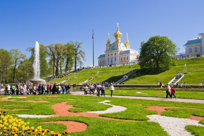I turisti visitano le viste del parco più basso di Peterhof immagini stock