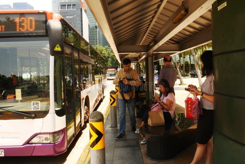 i väntan på att en stadsbuss anländer till Singapore arkivfoto