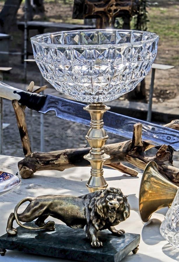 I vasi a cristallo d'annata con i supporti del metallo sotto forma di sculture sono venduti al mercato delle pulci fotografia stock libera da diritti