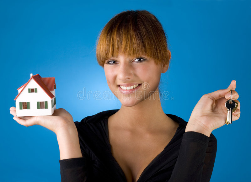 I've got my keys and my house. Beautiful woman with house miniature in hand and with keys in other. Smiling and looking at camera. Blue background, front view stock images