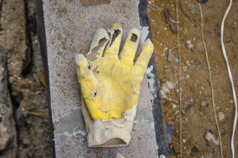 I vecchi guanti sporchi lacerati della mano del lavoratore hanno abbandonato su terra concreta fotografia stock libera da diritti