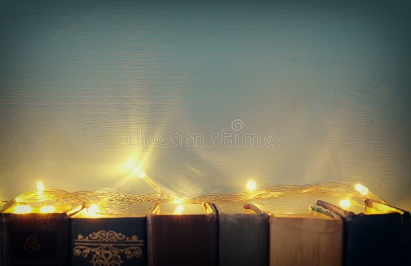 I vecchi libri sullo scaffale con la ghirlanda dell'oro si accende Copi lo spazio fotografia stock libera da diritti