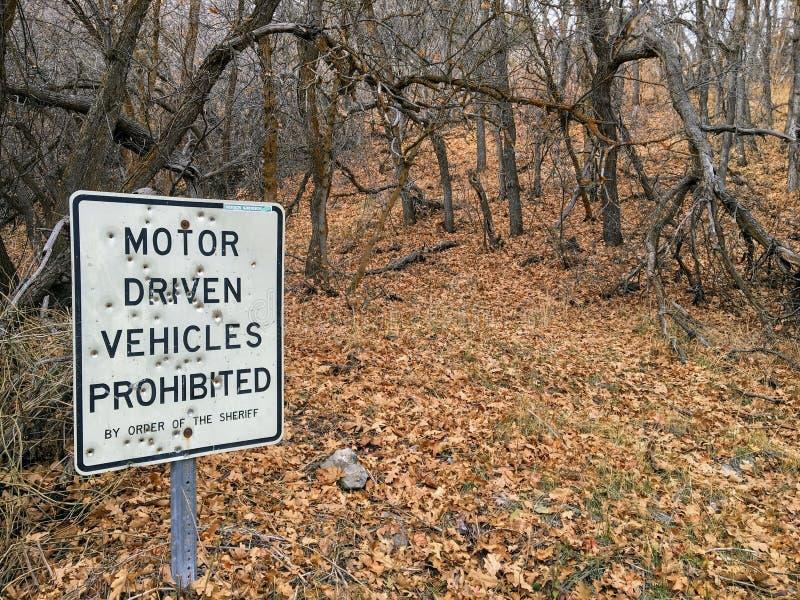 I veicoli con comando a motore proibiti per ordine dello sceriffo firmano con i fori di pallottola, nella traccia della foresta s fotografia stock