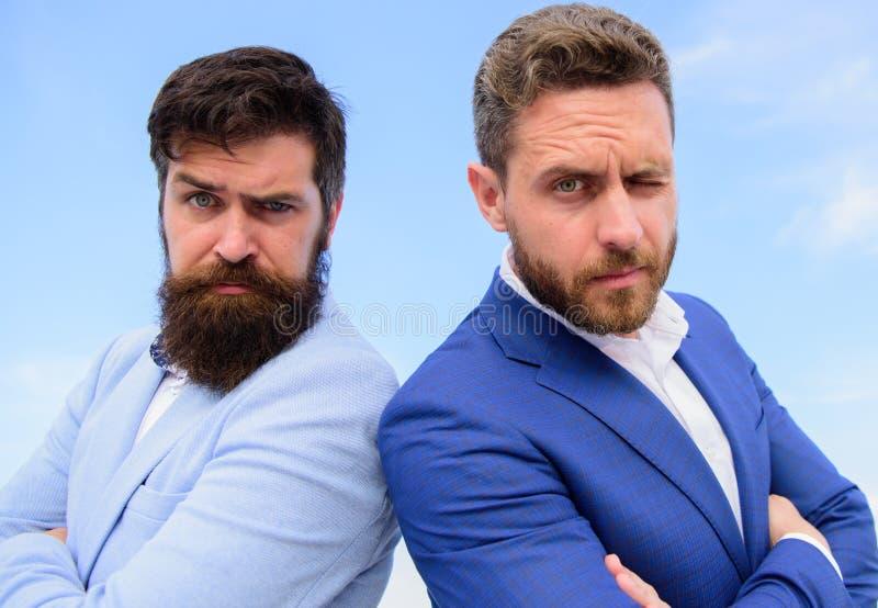 I vestiti convenzionali degli uomini stanno indietro per appoggiare il fondo del cielo blu Capi sicuri degli imprenditori Come sv immagini stock