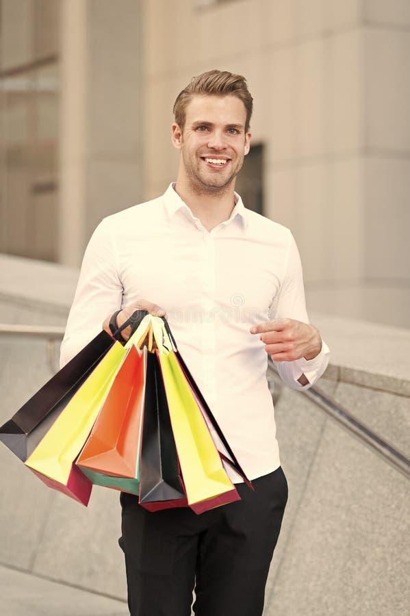 I vestiti convenzionali dell'uomo portano i sacchetti della spesa Il tipo felice porta i sacchetti della spesa del mazzo Affari p fotografia stock libera da diritti
