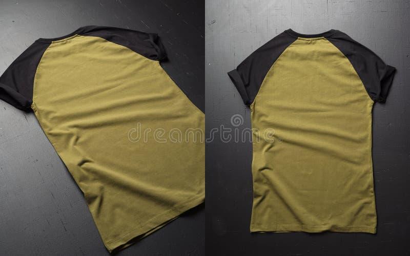 I vestiti d'annata della maglietta del cotone di colore del popolare due deridono su sul fondo di legno scuro di lerciume Vista p immagini stock libere da diritti