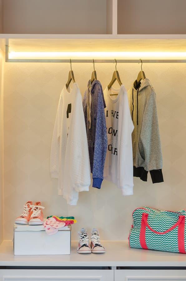 Download I Vestiti Del Bambino Che Appendono Sullo Scaffale Con Le Scarpe Ed I Calzini Fotografia Stock - Immagine di boutique, abbigliamento: 55362754