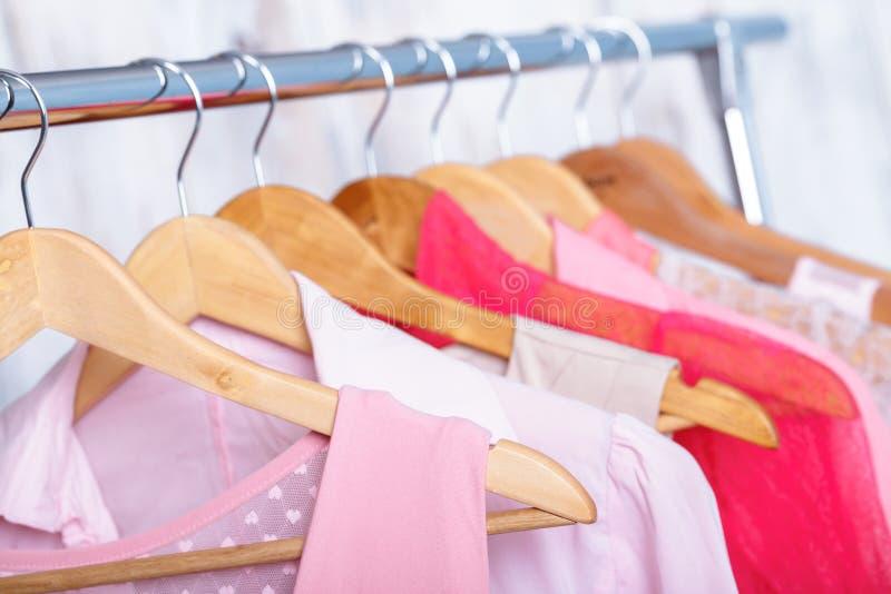 I vestiti delle donne rosa sui ganci sullo scaffale nel deposito di modo armadio immagini stock