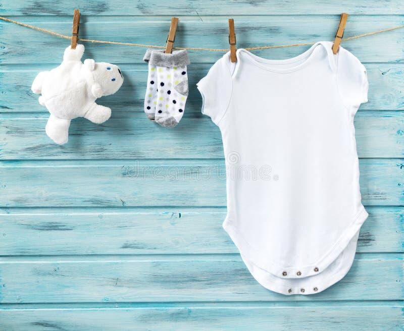 I vestiti e l'orso bianco del neonato giocano su una corda da bucato immagine stock libera da diritti