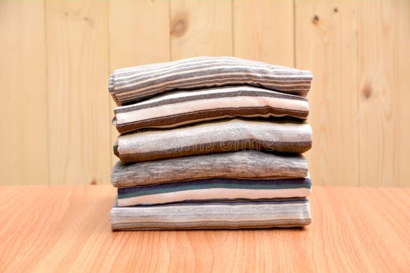 I vestiti hanno piegato ordinatamente sulla tavola di legno e sul fondo di legno immagini stock