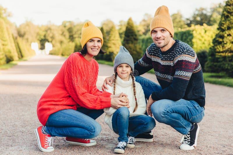 I vestiti tricottati usura amichevole della famiglia, hanno insieme passeggiata, ammirano il tempo splendido di autunno Giovani g fotografia stock