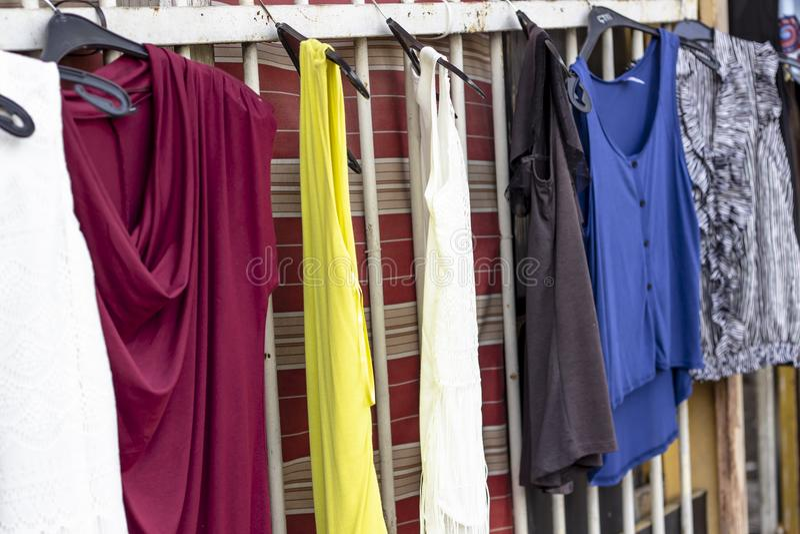I vestiti variopinti hanno appeso sulle barre di metallo che sono pronte ad essere venduto vicino alla via fotografia stock