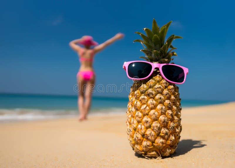 I vetri allegri dell'ananas e una donna in un bikini che prende il sole sulla spiaggia sul backgrounde del mare tirano sul fondo d immagine stock