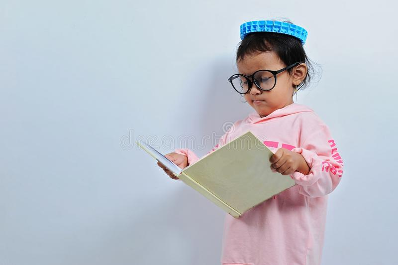 I vetri asiatici tagliati di usura della ragazza poi aprono un libro e leggono un libro seriusly immagine stock libera da diritti