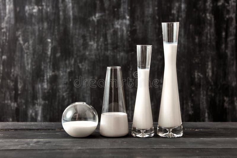 I vetri con il prodotto lattiero-caseario mungono la condizione su una tavola di legno nera sul nero Prodotto lattiero-caseario o immagine stock