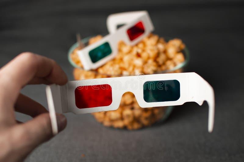 i vetri 3D e la bugia kitsch del popcorn in una lastra di vetro su un letto grigio, una persona mette sopra i vetri fotografia stock libera da diritti