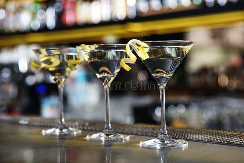 I vetri del limone cadono il cocktail di martini sul contatore della barra fotografia stock libera da diritti