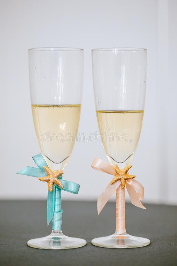 I vetri di Champagne per lo sposo e la sposa, coppie accoppiano la progettazione, le stelle marine ed il nastro fotografie stock