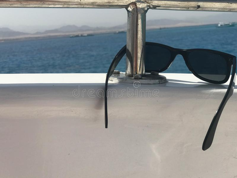 I vetri di plastica Sun-protettivi protettivi neri appendono sul berillo a bordo di una nave, di un yacht e di una barca a vela t immagini stock