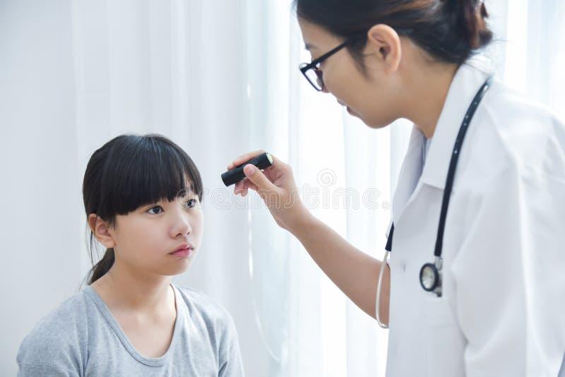 I vetri di usura di medico che controllano un paziente della bambina osserva immagine stock