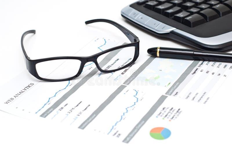 I vetri e la penna su un analytics stampato di Web segnalano immagine stock