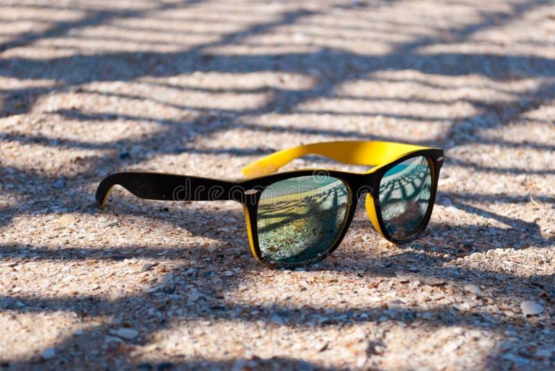 I vetri gialli luminosi con una struttura nera e di lenti colorate multi si trovano sulla sabbia all'ombra della griglia Nella ri fotografia stock