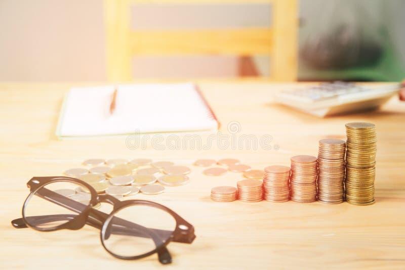 I vetri, monete d'argento disposte in mucchi sullo scrittorio con il fondo leggero di tramonto fotografia stock libera da diritti