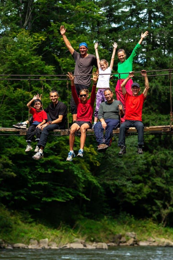 I viaggiatori felici, amici con a braccia aperte si siedono sul Br della sospensione fotografia stock libera da diritti