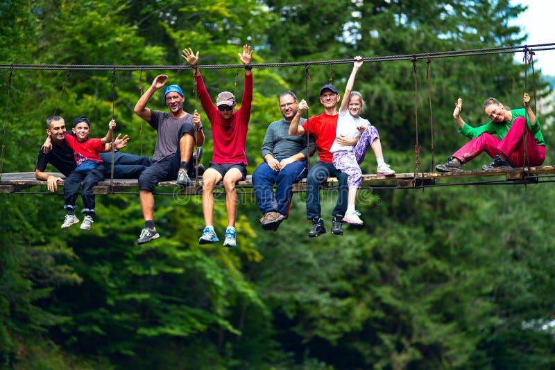 I viaggiatori felici, amici si siedono sul ponte sospeso immagine stock libera da diritti
