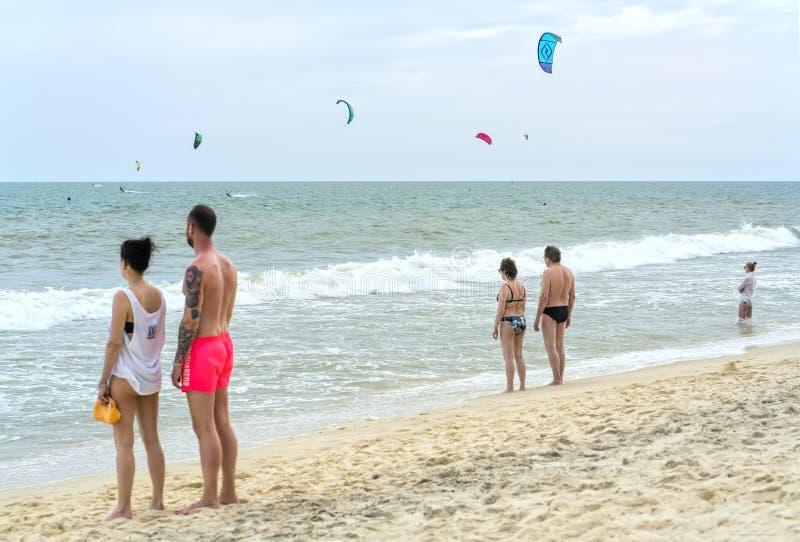 I viaggiatori stanno guardando i surfisti dell'aquilone fotografia stock