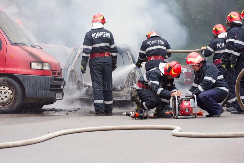 I vigili del fuoco estingue l'automobile su fuoco ed altri due stanno preparando gli strumenti di liberazione immagini stock