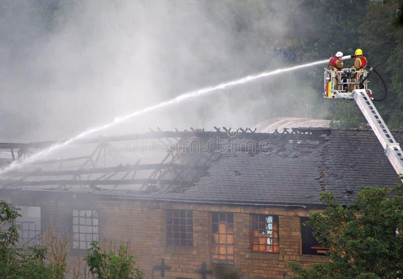 I vigili del fuoco su una piattaforma elevata che mette fuori il fuoco ai precedenti walkeys ostruisce il mulino dentro hebden il fotografia stock